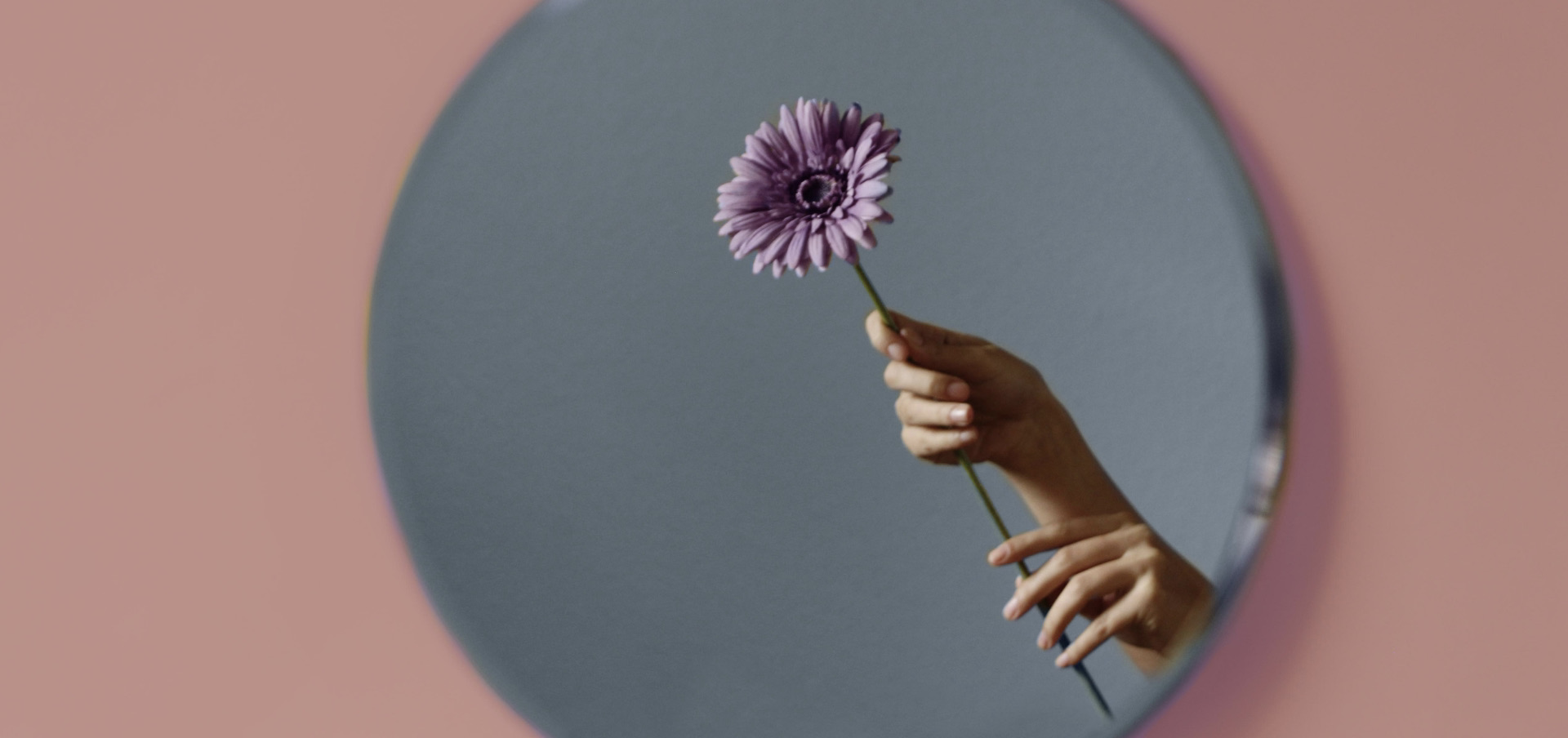 a person holding a flower and looking in the mirror