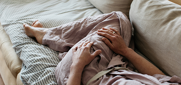 woman lying on a couch not feeling well