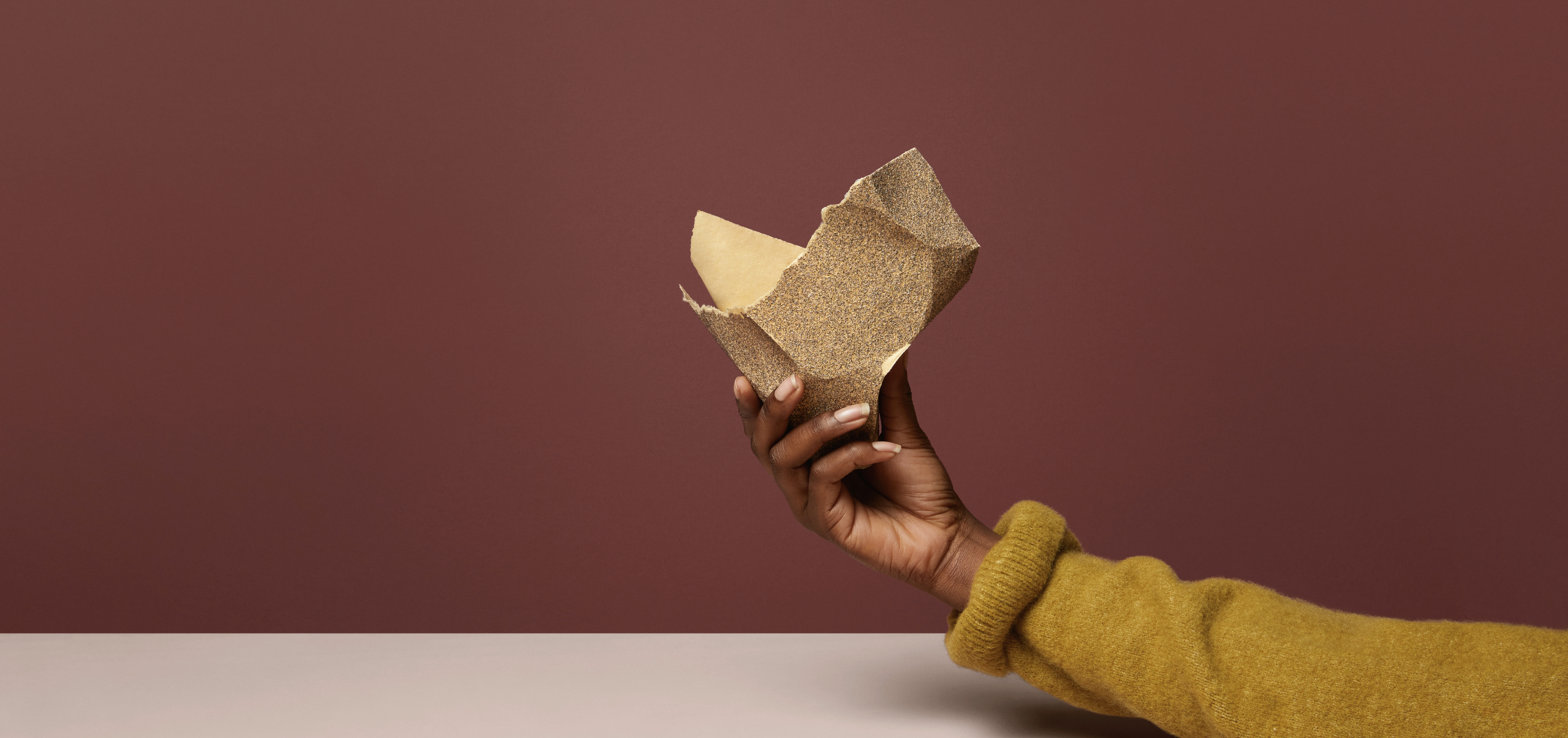 a person's hand, holding itchy sandpaper