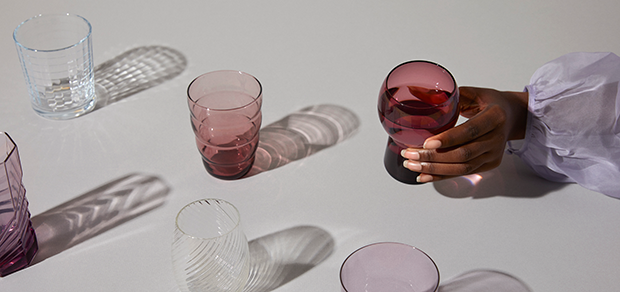 assorted glasses and woman's hand