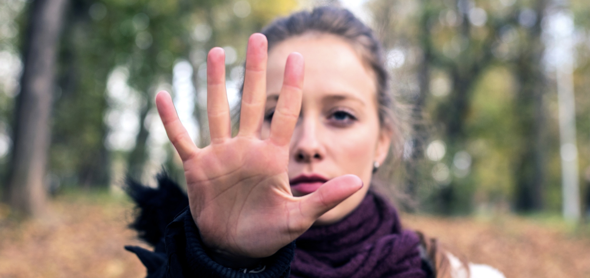 a woman holding up her hand to signal stop