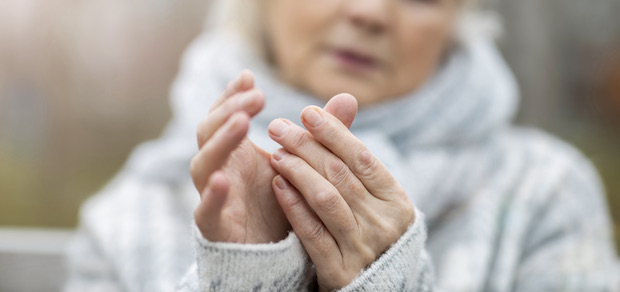 women looking at her hand while experiencing joint pain