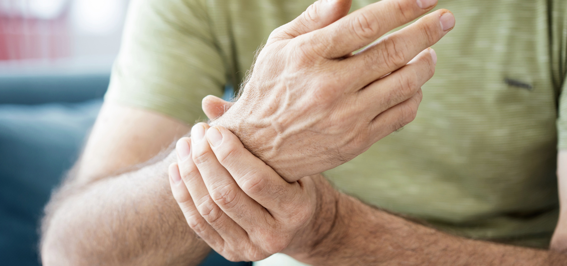 a man experiencing joint pain grabbing his wrist