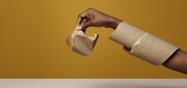 hand holding sandpaper, with sandpaper wrapped around the arm