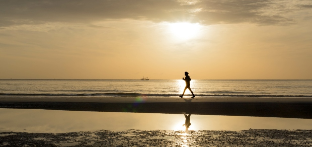 The silhouette of a person running on the beach at sunset.