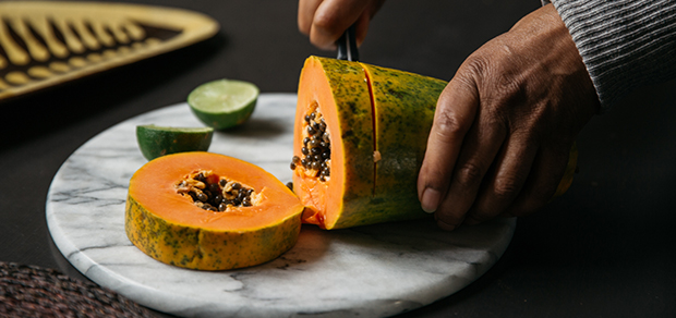 woman cutting a melon for a healthy snack