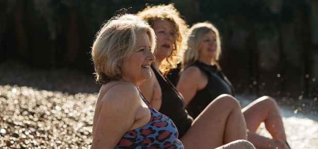 middle-aged women who are friends sitting on a beach